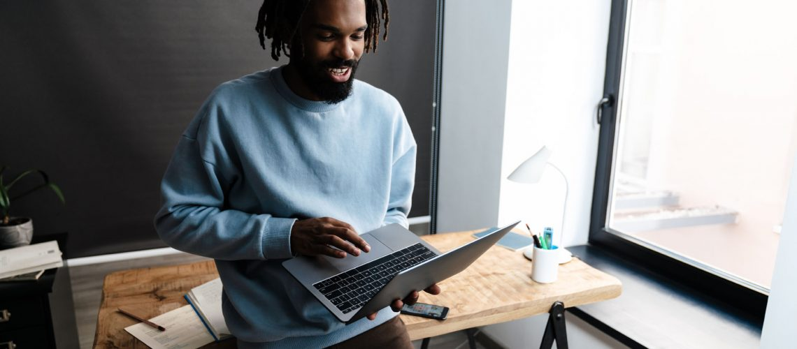 Confident afro american man working on laptop computer while leaning on a desk